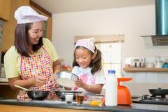 Den asiatiska familjen tycker om framställning pannkakan, den asiatiska modern och dotterenj Royaltyfri Fotografi