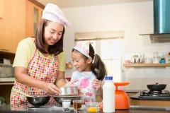 Den asiatiska familjen tycker om framställning pannkakan, den asiatiska modern och dotterenj Arkivbilder
