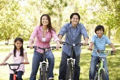 Den asiatiska familjridningen cyklar parkerar in Arkivbild