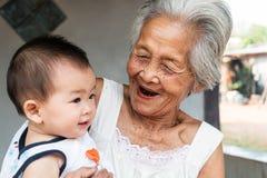 Den asiatiska farmodern med behandla som ett barn Royaltyfria Foton