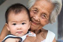 Den asiatiska farmodern med behandla som ett barn Royaltyfria Bilder