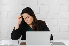 Den asiatiska feta affärskvinnan sitter angeläget i kontoret royaltyfri bild