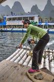 Den asiatiska flickaferrymanen korsar floden på flotten med motorn, Kina Royaltyfria Foton