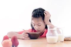 Den asiatiska flickan önskar inte att äta hans frukost arkivfoto