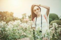 Den asiatiska flickan att koppla av tycker om ferie med fotografiblommahobby i parkerar arkivbild