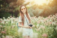 Den asiatiska flickan att koppla av tycker om ferie med fotografiblommahobby i parkerar arkivfoton
