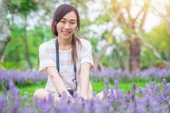 Den asiatiska flickan att koppla av tycker om ferie med fotografiblommahobby i parkerar fotografering för bildbyråer