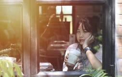 Den asiatiska flickan drack jag en smoothiechoklad i en coffee shop royaltyfri fotografi