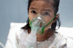 Den asiatiska flickan har astma, eller lunginflammationsjukdom- och behovsnebulizationen får förbi inhalatormaskeringen på hennes arkivfoto
