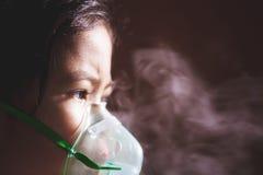 Den asiatiska flickan har astma, eller lunginflammationsjukdom- och behovsnebulizationen får förbi inhalatormaskeringen på hennes fotografering för bildbyråer
