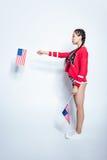 Den asiatiska flickan, i rött anseende och att göra en gest för tröja med lilla USA, sjunker Royaltyfri Foto