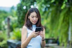 Den asiatiska flickan kopplar av i trädgården med hennes mobiltelefon Arkivfoto