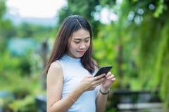 Den asiatiska flickan kopplar av i trädgården med hennes mobiltelefon Arkivfoton