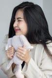 Den asiatiska flickan kramar hennes docka royaltyfri bild