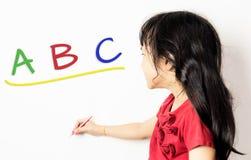 Den asiatiska flickan lär det engelska abc:et Royaltyfri Foto
