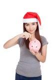 Den asiatiska flickan med den röda santa hatten satte ett mynt till den rosa spargrisen Arkivfoton