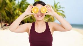 Den asiatiska flickan med h?rlig klar hud rymmer frukter p? stranden med havsbakgrund - h?lso- och viktf?rlustbegreppet arkivbild