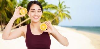 Den asiatiska flickan med h?rlig klar hud rymmer frukter p? stranden med havsbakgrund - h?lso- och viktf?rlustbegreppet royaltyfria bilder