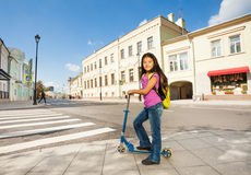 Den asiatiska flickan med långt hår står på sparkcykeln Arkivbild