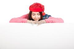Den asiatiska flickan med röd julhattblick vilar ner hennes haka på bla Arkivfoton
