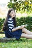 Den asiatiska flickan och skolboken i toothy le för hand vänder mot med happ Arkivfoton