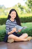 Den asiatiska flickan och skolboken i toothy le för hand vänder mot med happ Arkivbilder