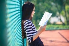Den asiatiska flickan och skolboken i toothy le för hand vänder mot med happ Royaltyfri Bild