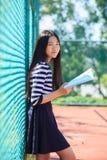 Den asiatiska flickan och skolboken i toothy le för hand vänder mot med happ Royaltyfria Bilder