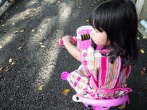 Den asiatiska flickan på en rosa klänning med en ny rosa färg cyklar Hon är le och lycklig att få en ny cykel arkivbild