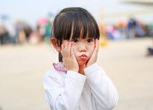 Den asiatiska flickan poserar att trycka på kinden och att se royaltyfri foto