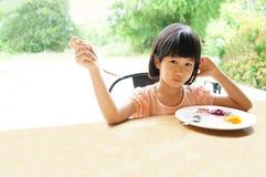 Den asiatiska flickan 6s äter frukostmålplattan sitter i tabell Fotografering för Bildbyråer
