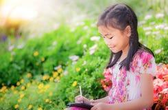 Den asiatiska flickan skriver en anteckningsbok Fotografering för Bildbyråer