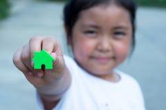 Den asiatiska flickan som spelar husmodellen, väljer fokusen Fotografering för Bildbyråer