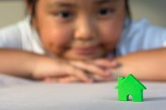Den asiatiska flickan som spelar husmodellen, väljer fokusen Royaltyfria Foton