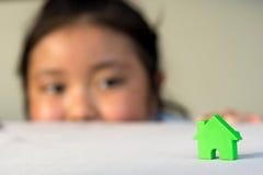 Den asiatiska flickan som spelar husmodellen, väljer fokusen Arkivfoto