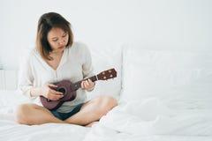 Den asiatiska flickan spelar gitarren från morgonvaken upp Framställning det att känna sig ljus och rogivande musik kan framkalla fotografering för bildbyråer
