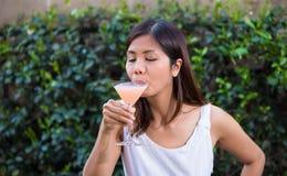 Den asiatiska flickan tycker om en martini Royaltyfri Fotografi