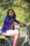Den asiatiska flickaridningcykeln parkerar offentligt med grönt oskarpt bakgrundsbruk som för som kan användas till mycket i sunt  Royaltyfri Bild