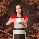 den asiatiska fokusen för koppen för bakgrundsbaristakaffe isolerade servingen som visar den le servitrisen vitt kvinnabarn Ungt  royaltyfria foton