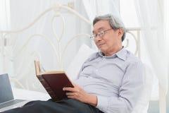 Den asiatiska gamal manexponeringsglasprofessorn tycker om att läsa läroboken fotografering för bildbyråer