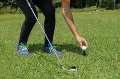Den asiatiska golfflickan satte golf på utslagsplats i grön golfbana arkivfoton
