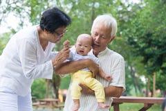 Den asiatiska gråt behandla som ett barn tröstat av morföräldrar Royaltyfri Foto