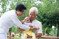 Den asiatiska gråt behandla som ett barn tröstat av morföräldrar Arkivbilder