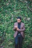 Den asiatiska grabben som bär en brun dräkt på väggen, är träd Royaltyfria Foton