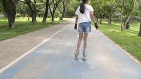 Den asiatiska gulliga flickan som spelar rullblad på vägen på allmänhet, parkerar arkivfilmer