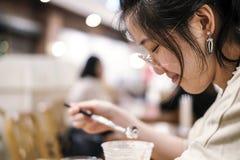 Den asiatiska gulliga kvinnan som dricker chokladfrappe i kafé, shoppar Royaltyfria Bilder