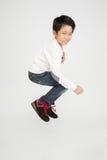 Den asiatiska gulliga pojken hoppar med leendeframsidan Royaltyfria Bilder