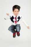 Den asiatiska gulliga pojken hoppar med leendeframsidan Royaltyfri Bild
