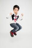 Den asiatiska gulliga pojken hoppar med leendeframsidan Royaltyfri Foto