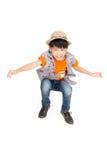 Den asiatiska gulliga pojken hoppar med leendeframsidan Arkivfoton